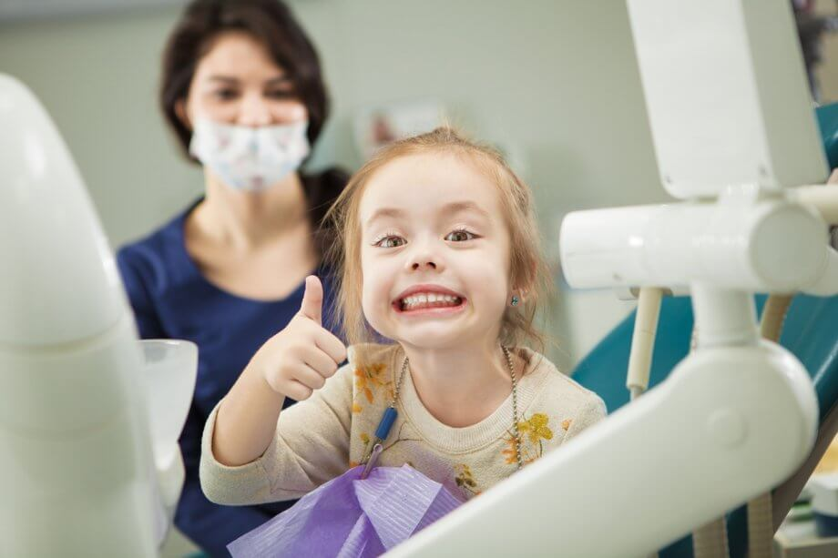 Photograph of a young girl with straight red hair smiling and giving a thumbs up while at the dentist.