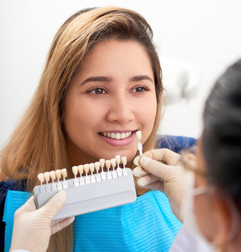 Dentist Picking Shade Of veneers For Patient To Improve Smile